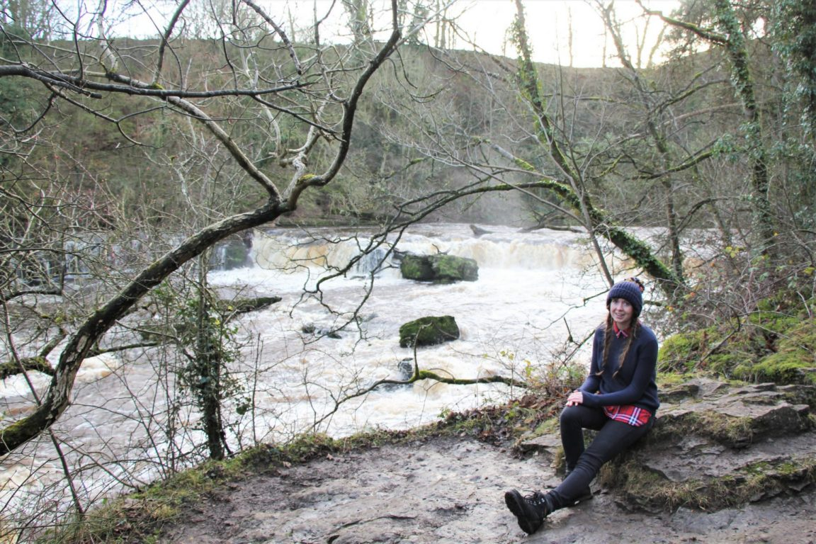 Girl sits by Aysgarth Upper Waterfall in North Yorkshire in winter